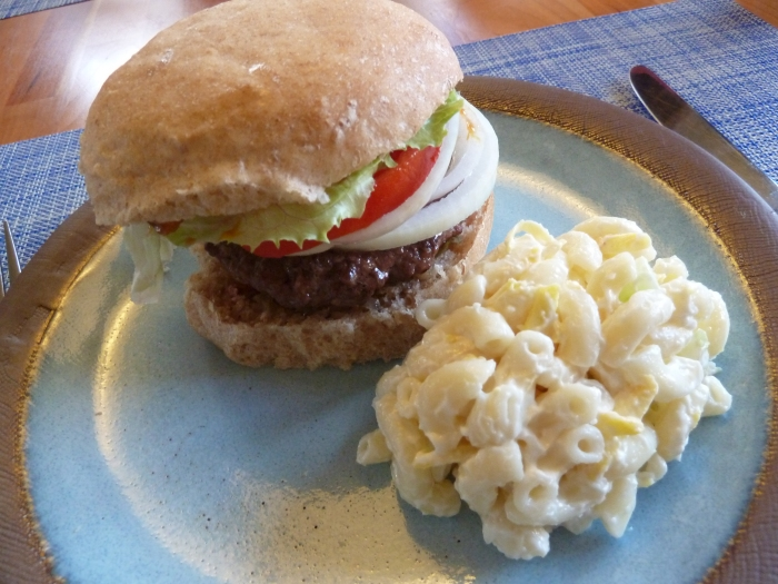 Grass-fed, locally-raised beef burger on a homemade bun with Kaua'i grown lettuce, tomato and onion with a side of Hawaiian-style mac salad.
