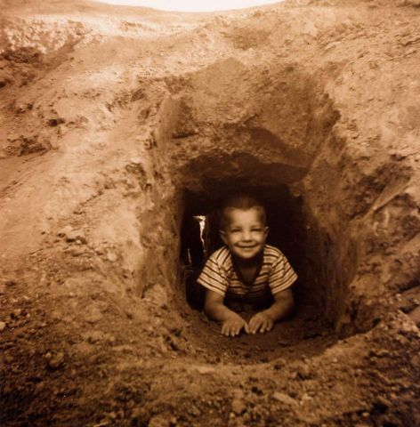 boy crawling out of a dirt tunnel