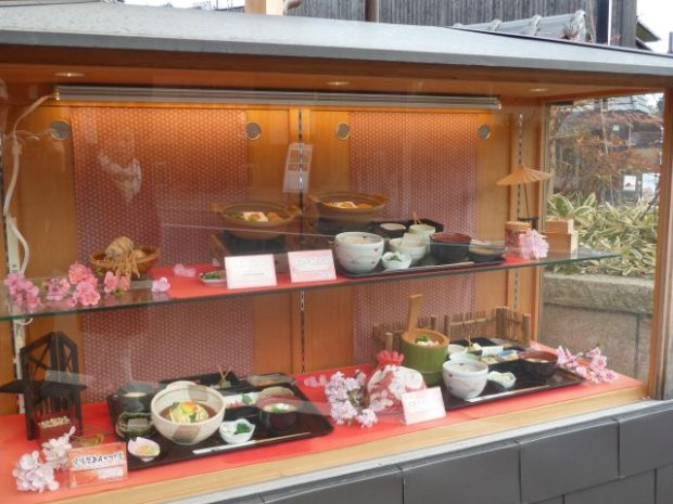 Japanese restaurants often present their menu outside using realistic plastic models of the items. If you don't speak Japanese, you can take your waiter outside and point to what you want.
