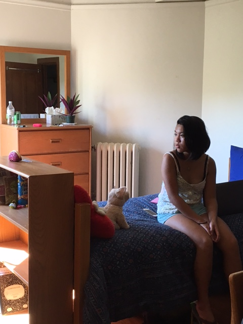 A pensive WenYu in her dorm room, taking it all in