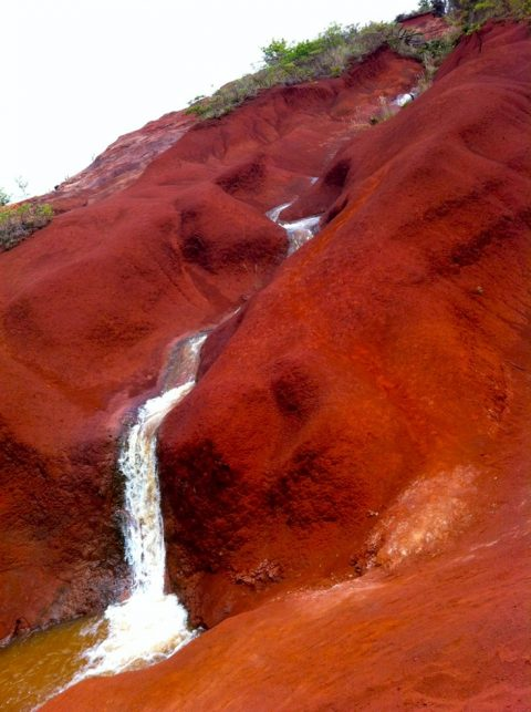 Red dirt waterfall beside the road on the way to the canyon