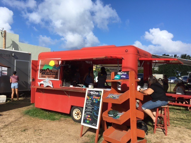 Wailua Shave Ice's little red trailer is located on the makai (ocean) side of Kuhio Highway in Kapaa, on a vacant lot between two storefronts.