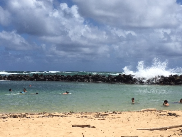 Waves crash over the rock wall surrounding the pool at Lydgate Beach Park.