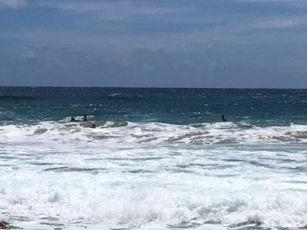 Surfers wait out past the rough surf