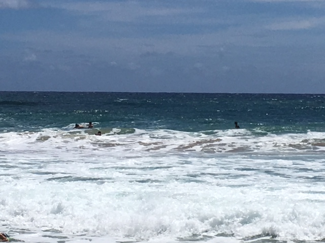 Surfers wait out past the rough surf