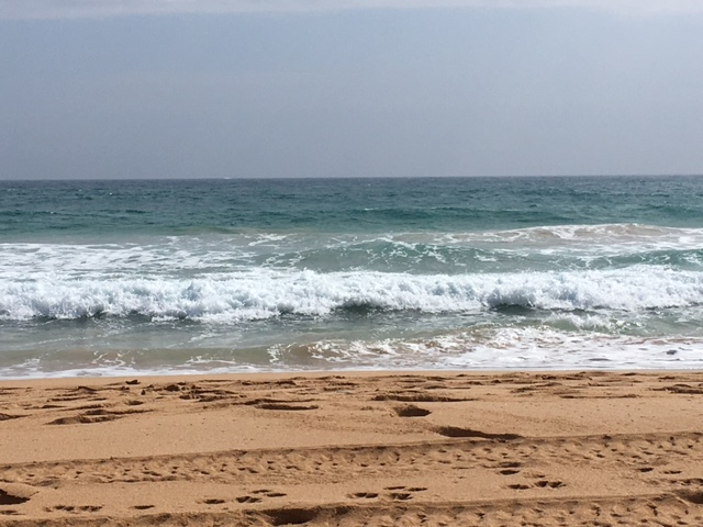 The view on Thursday. The surf is rougher, and the sky is gray from VOG