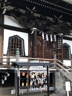 The front of the main temple includes a Shinto shimenawa, ema, and omikugi (fortunes)